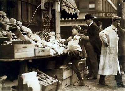 young-boy-working-at-fruit-veg-stand-on-streets-of-boston-massachusetts-nice-view-of-stores-people-walking-along-street-oct-1909s